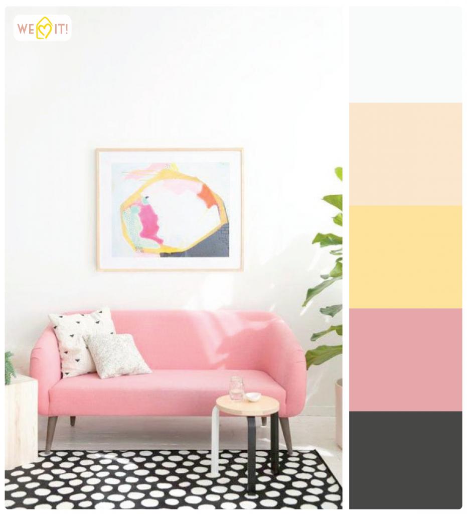 Uma sala super charmosa, com sofá rosa e quadro colorido.