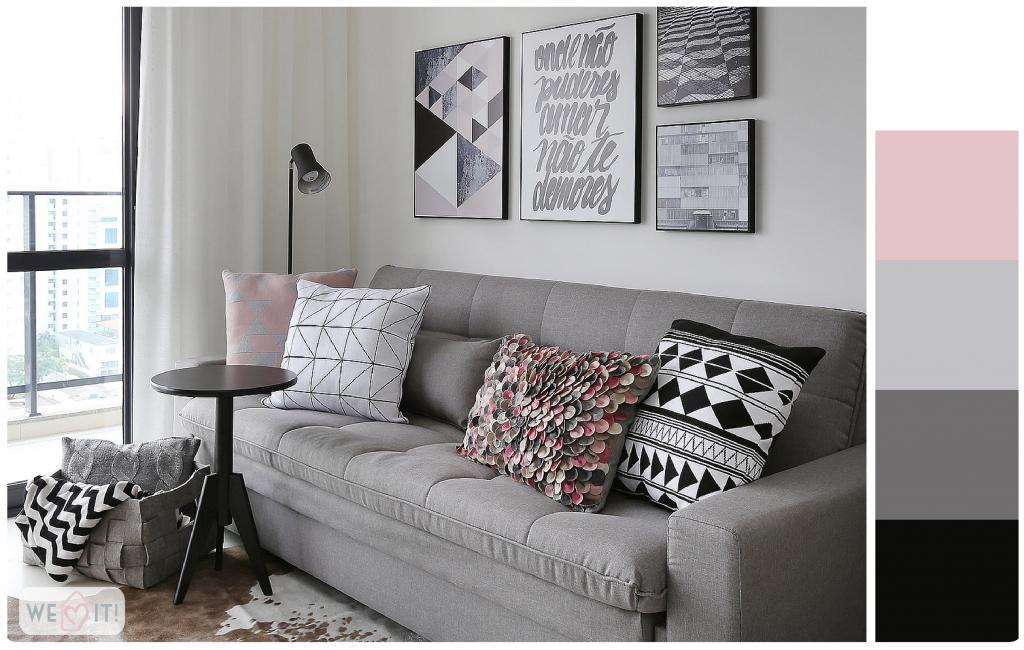 sala em tons de cinza, com almofadas e quadros.
