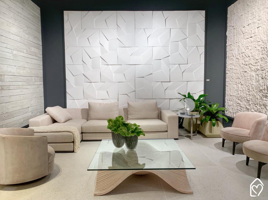 Sala de estar com sofá e poltronas. Revestimentos da Castelatto nas paredes