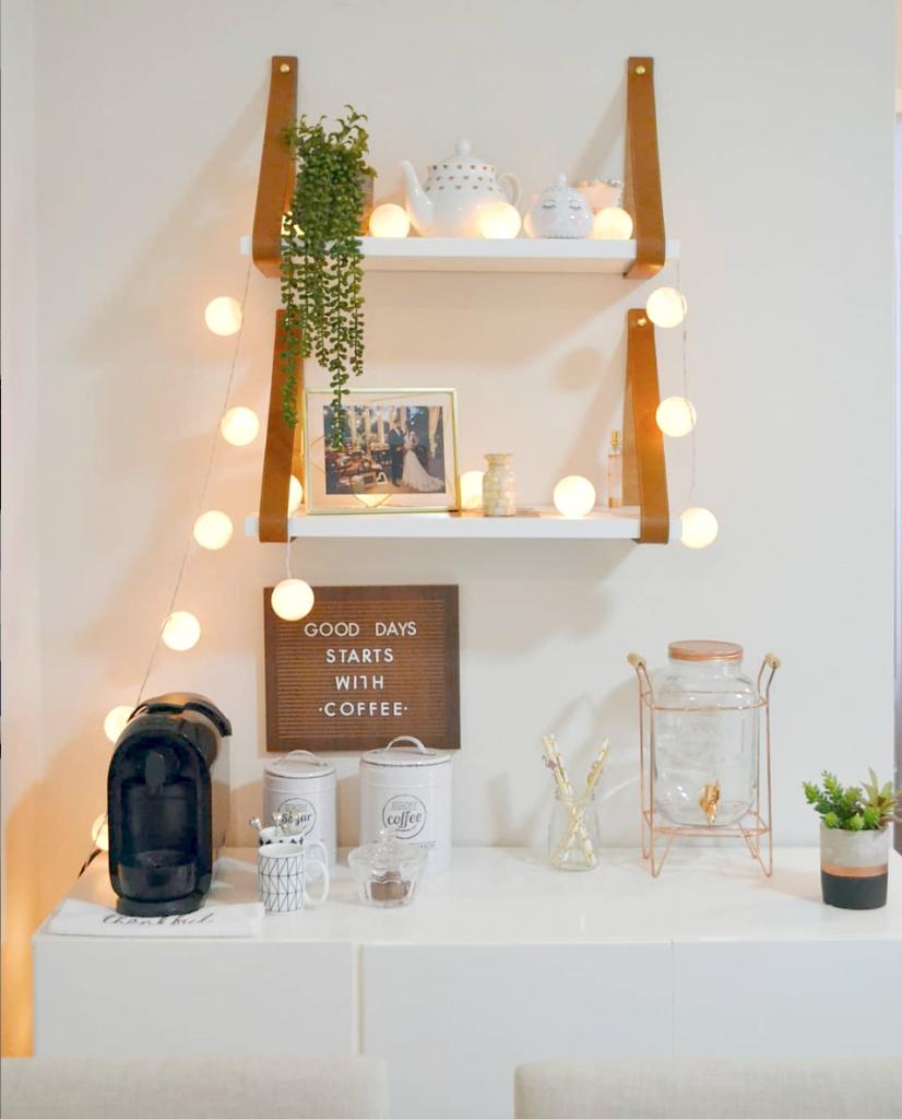 Espaço do café, com prateleiras, luzinhas e cafeteira .