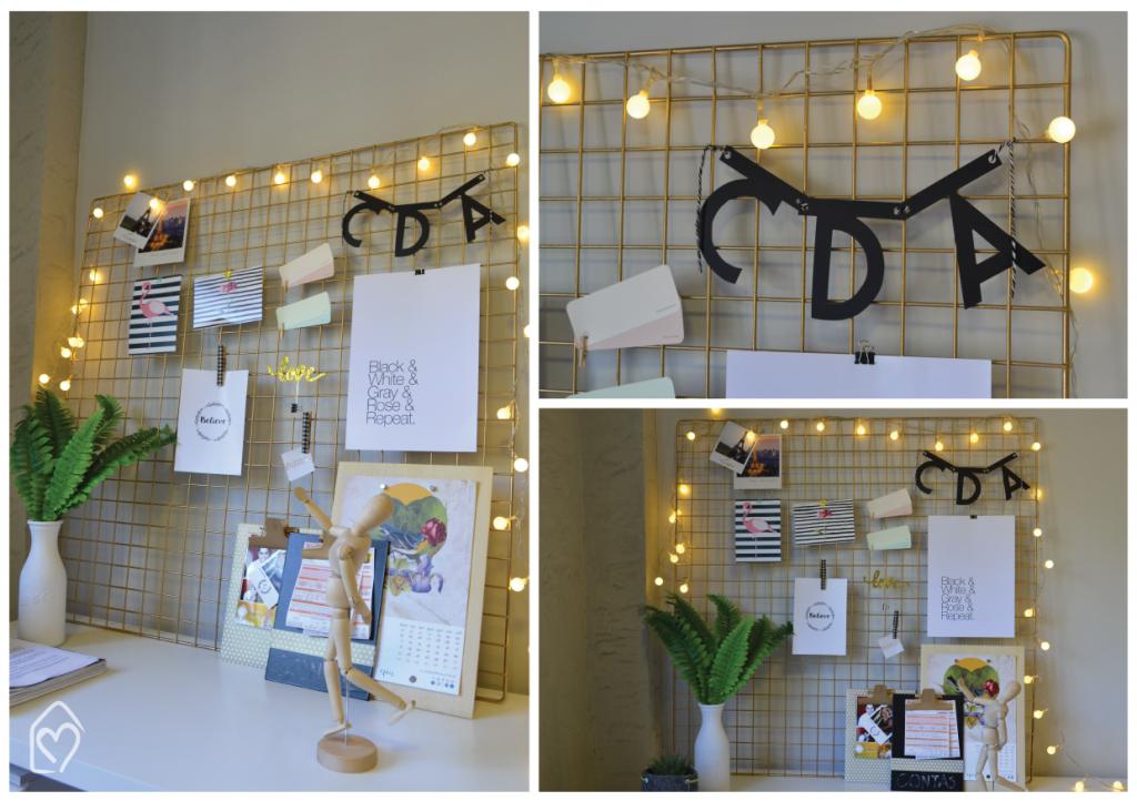 Moodboard com grid dourado, com frases inspiradoras, postais e recordações de viagens. Cordão de luzinhas traz charme pra decor.