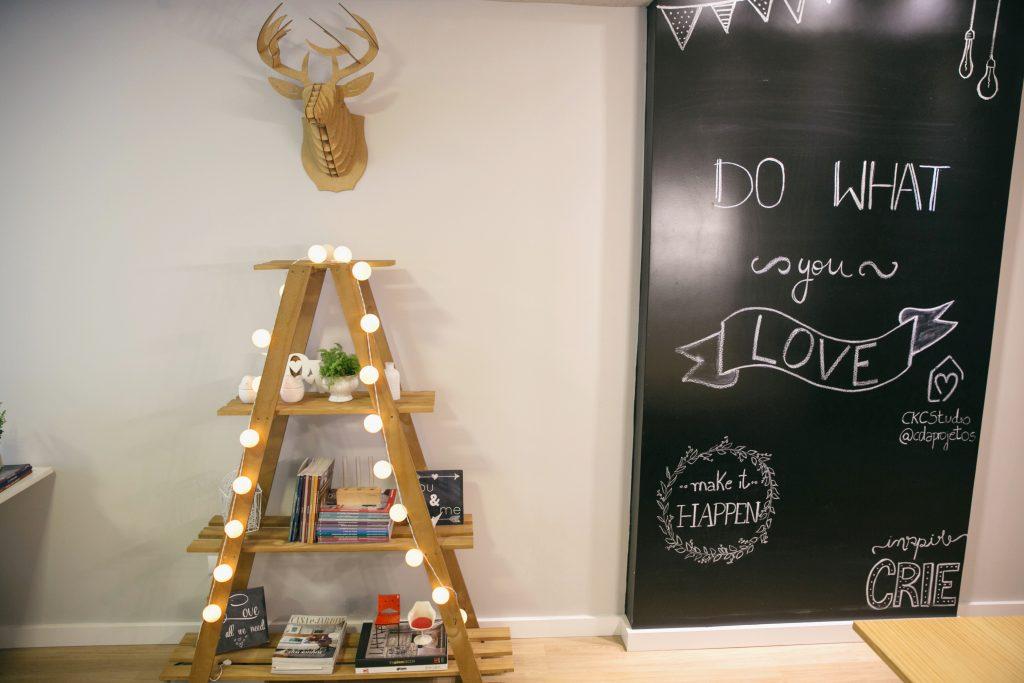 Escada decorativa que serve de estante, com objetos decorativos, livros e plantinhas. Parede lousa com arte em giz, do what you love.