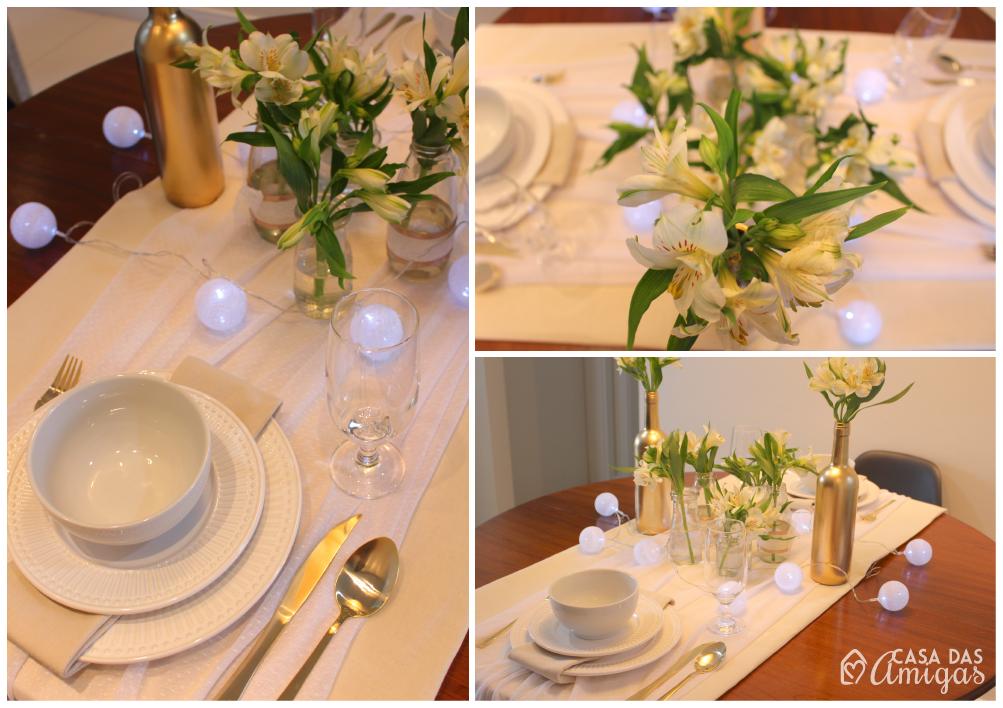 Mesa posta, com toalha branca, louça branca, talheres dourados, flores brancas e luzinhas pra completar da decoração.