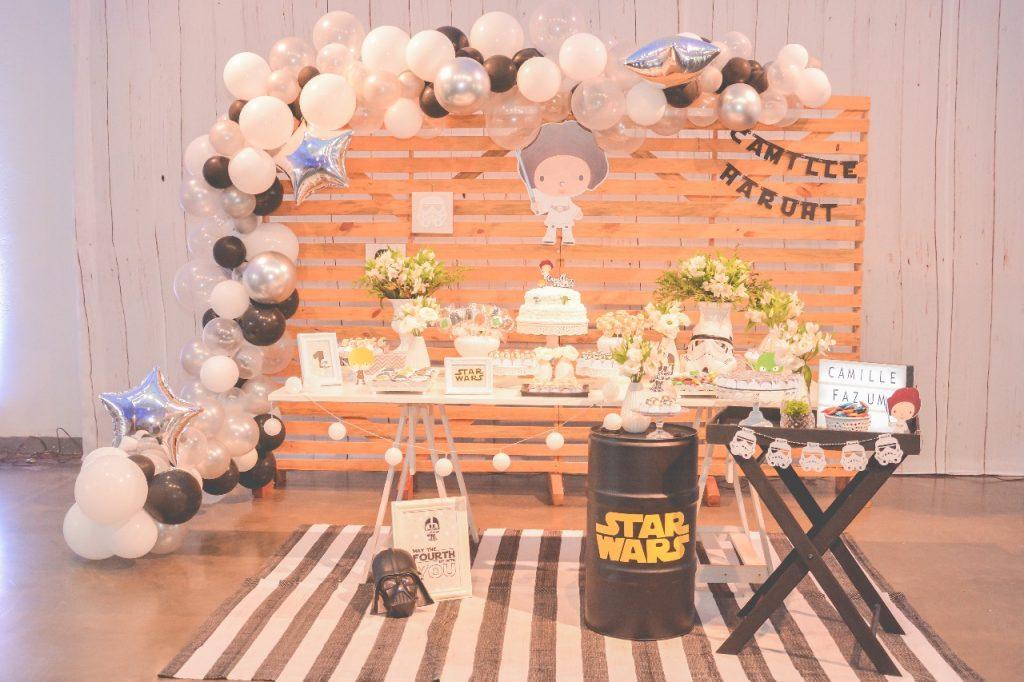 Festa infantil com tema star wars. Painel de fundo em madeira, com balões. Mesa de doces com flores e personagens do filme.