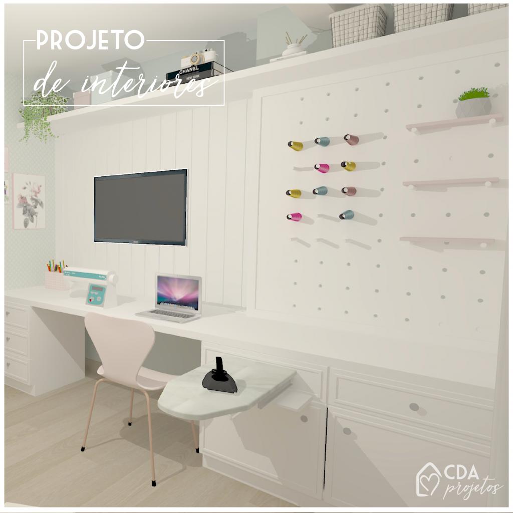 Painel branco com lambri e pegboard, para colocar a TV e organizar os itens de costura. A bancada serve de apoio para costura, notebook, e também com espaço para armazenamento.