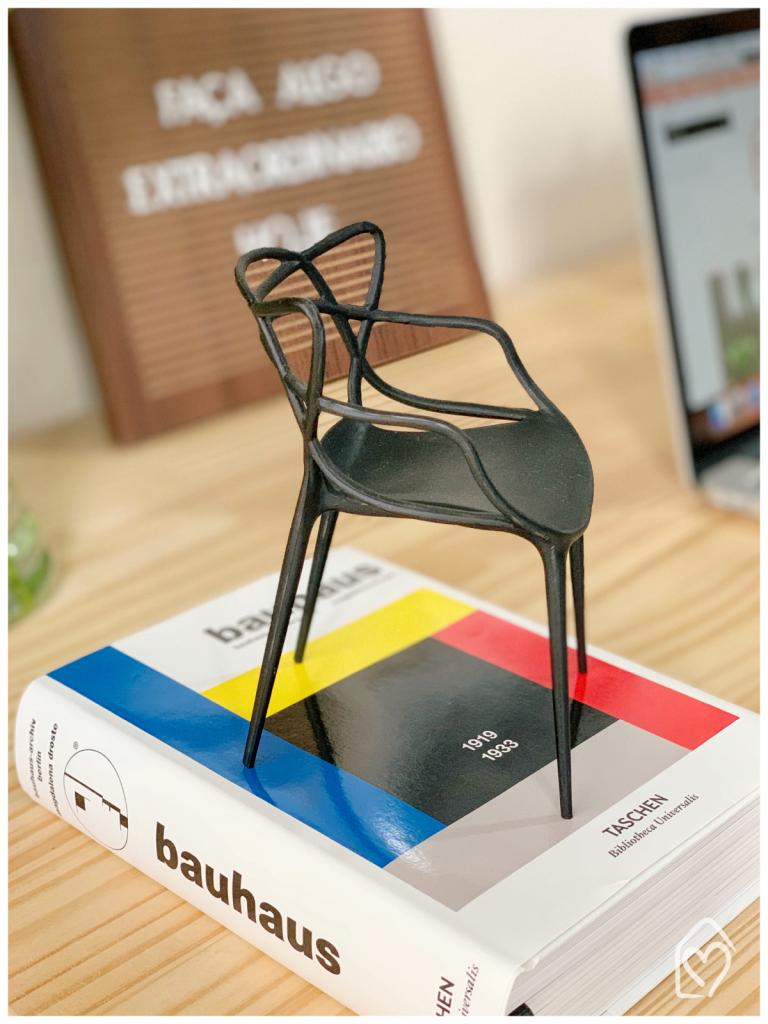 Livro bauhaus e cadeira de design decorativa, dois itens pra saber Como organizar a mesa do seu home office